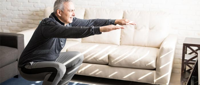 Man squatting in his living room