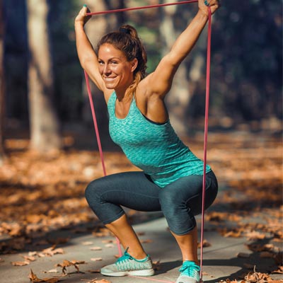person squatting with a resistance band
