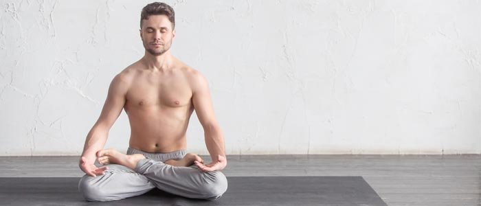 Person sat cross legged, experiencing the mental benefits of yoga