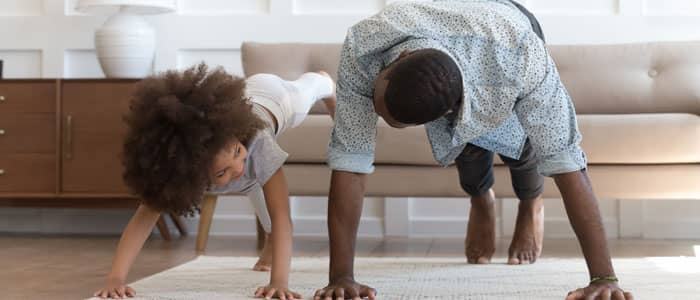 man and child using the sofa to do push ups together