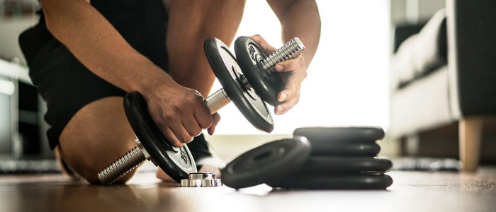 man adding weights to dumbbells