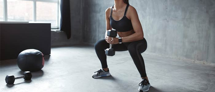 woman doing dumbbell goblet squats