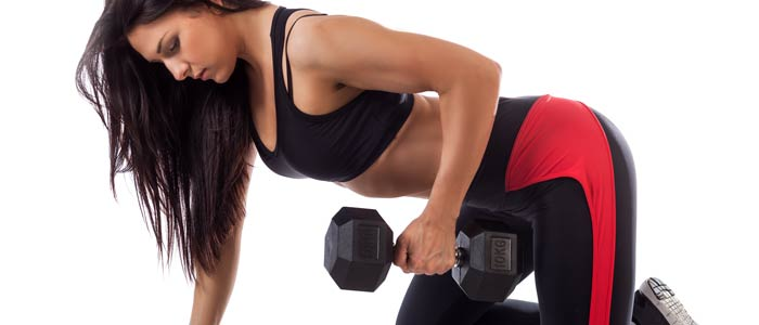 woman doing dumbbell kickbacks