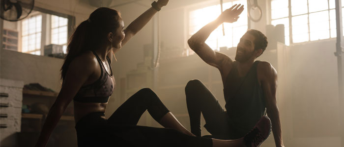 Man and woman high fiving in the gym