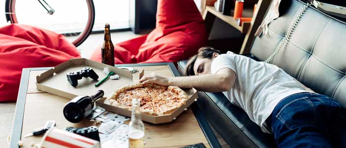 man asleep on the sofa with his hand in a pizza box