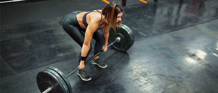 Woman crouching for a barbell lift