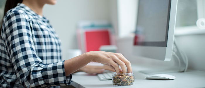 Woman at a desk eating seeds