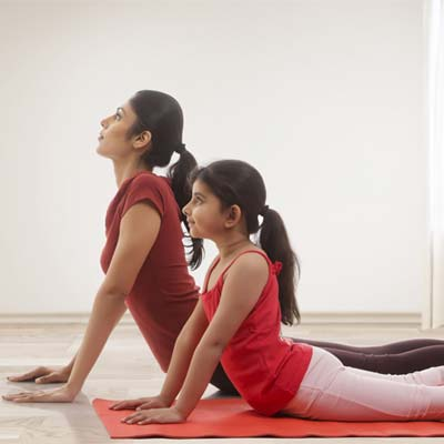 woman and child doing yoga poses to keep active