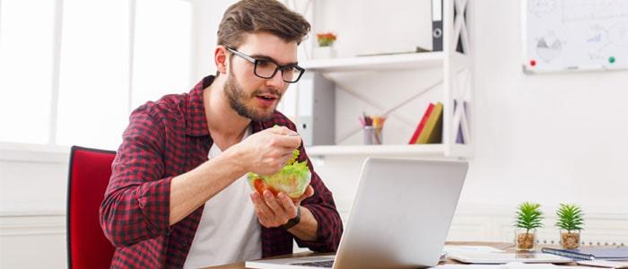 Man eating a salad at his desk