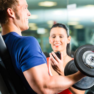 Man doing dumbbell lifts and being timed by a woman
