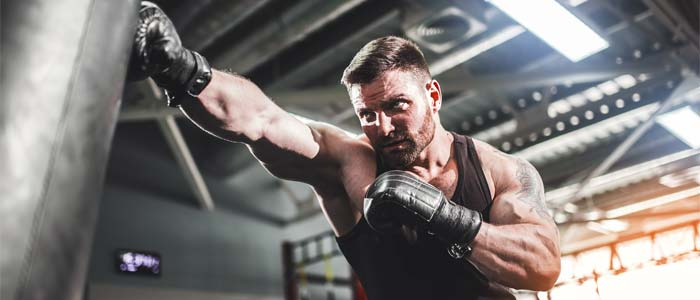 Man training with a boxing bag closer up
