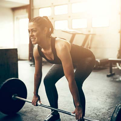 woman lifting barbell with weights