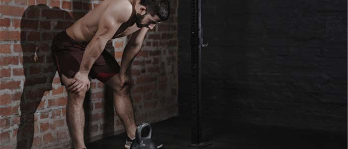 man leaning against the wall in a gym