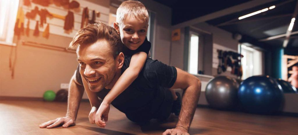 Man doing push ups with child on hos back