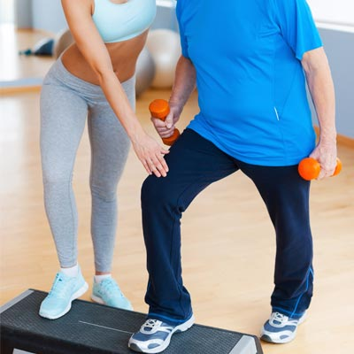 woman helping an older man exercise on an aerobic stepper