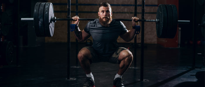 Man doing a shoulder press with a barbell and weights