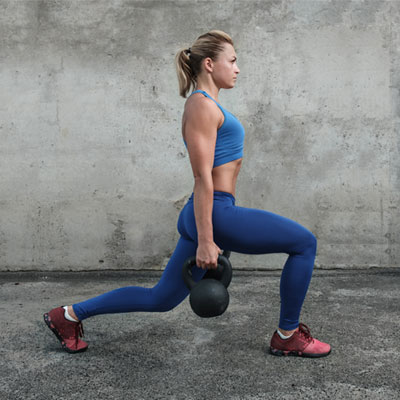 woman doing kettlebell lunges with pass