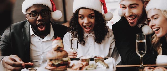 group of people in santa hats having christmas food