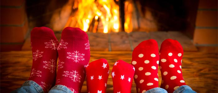 Family of socked feet in front of the fire