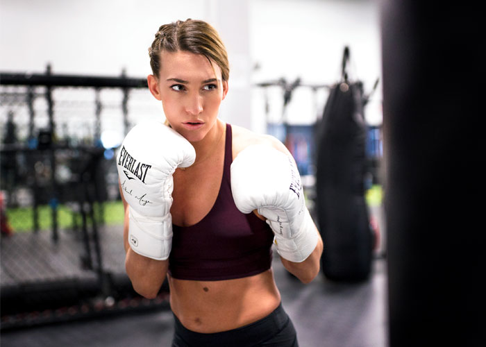 Woman wearing everlast gloves showing boxing stance
