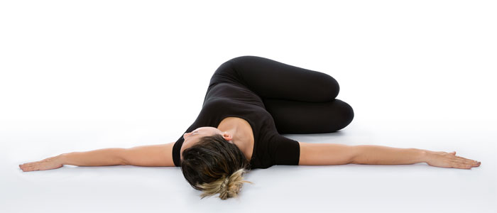 woman doing the yoga pose Supine Spinal Twist