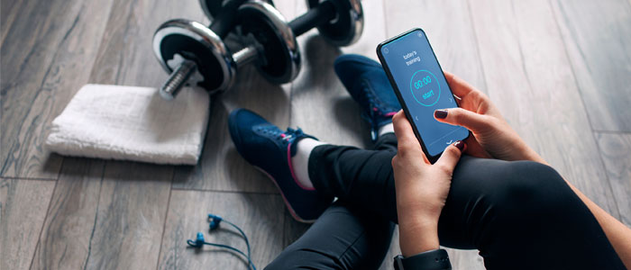 woman checking her fitness app on her phone