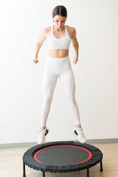 woman doing trampoline exercise straight leg jump