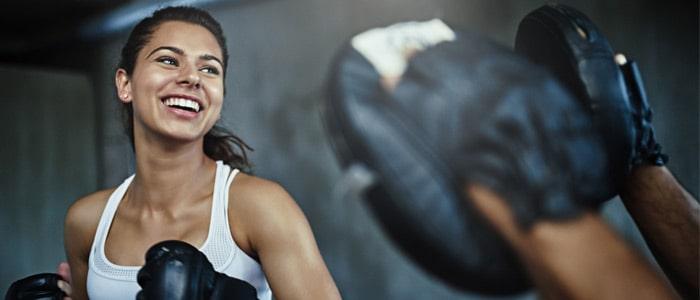 woman doing boxing training with another person