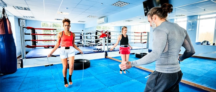 people training with skipping ropes in a boxing gym