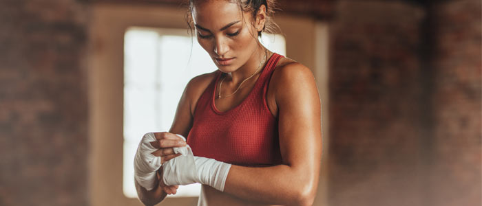 Woman wrapping boxing hand wraps around her hands.  boxing better cardio than running