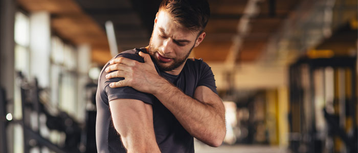 man holding his shoulder as if injured