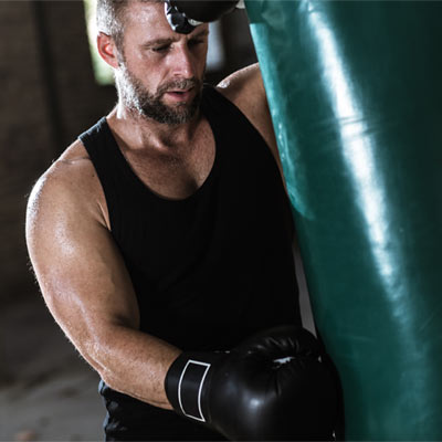 Man leaning against a boxing bag