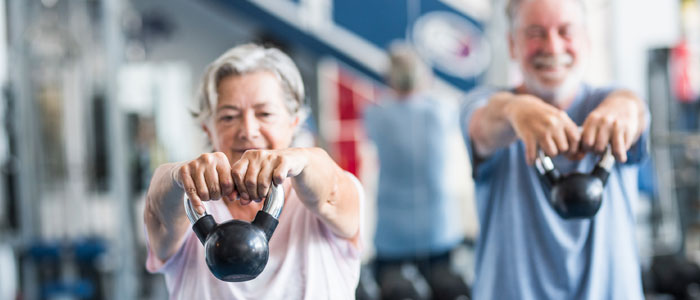 elderly couple lifting kettlebells