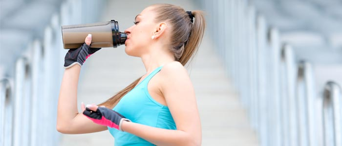 Woman outside drinking a protein shake during a workout