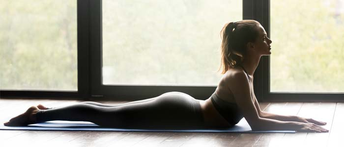 Woman doing back stretches on a yoga mat