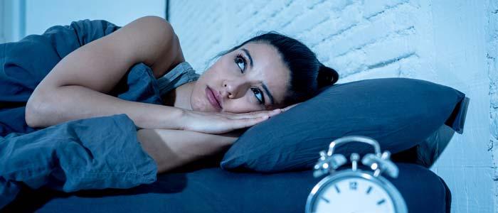 woman laid in bed awake, struggling to sleep