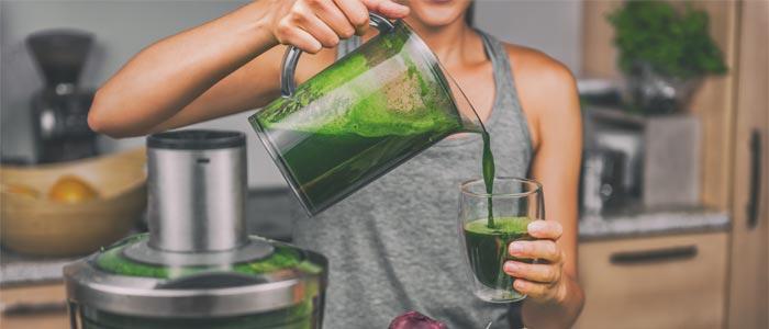 woman making a green detox smoothie