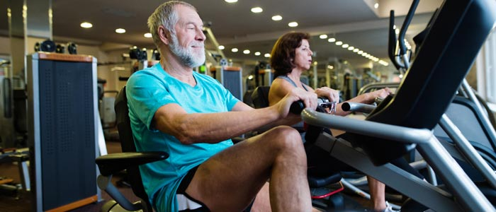 elderly man in a gym on a recumbent bike