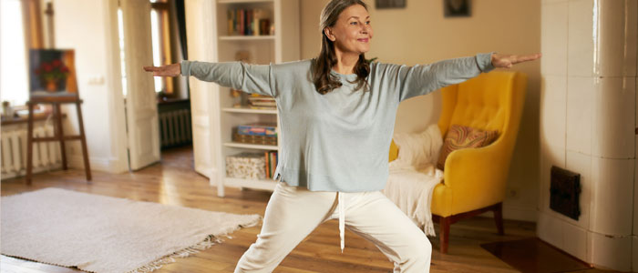 middle aged woman doing yoga at home