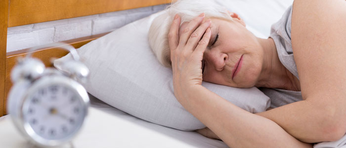 older woman in bed struggling to sleep