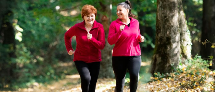 two older women jogging together outside