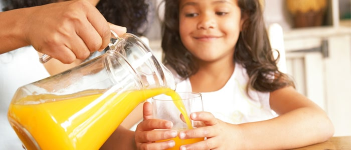 woman pouring orange juice into a glass being held by a little girl