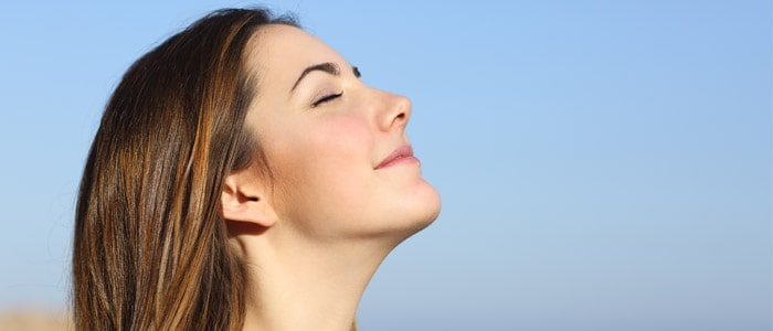 Woman breathing deeply outside to help with stress