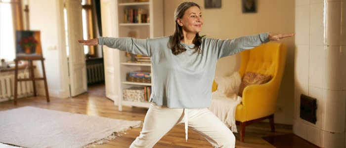 Woman practicing yoga in her living room