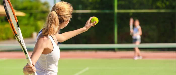 two women playing tennis outdoors