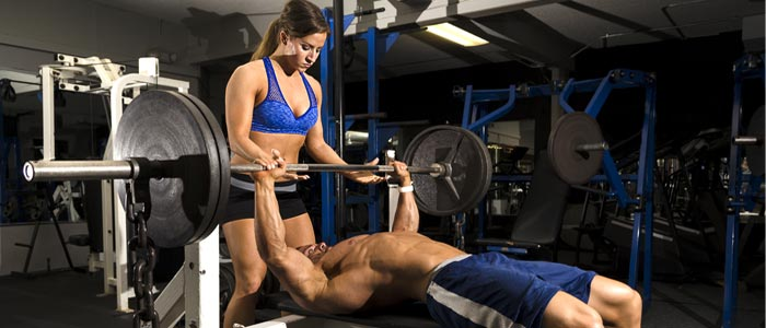 man doing bench presses with a woman spotter