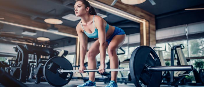 woman lifting weight on a barbell