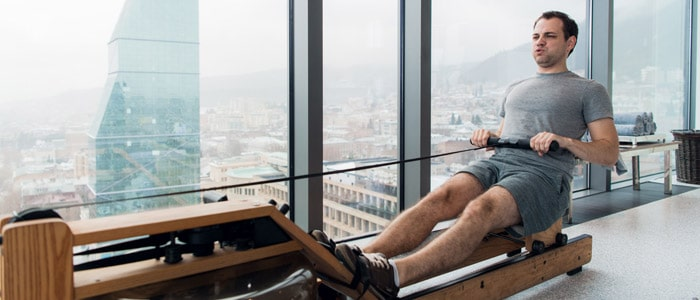 man rowing in his house on a rowing machine