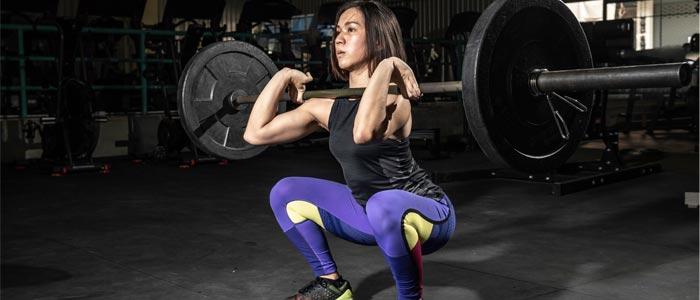 Woman doing a squat to shoulder press
