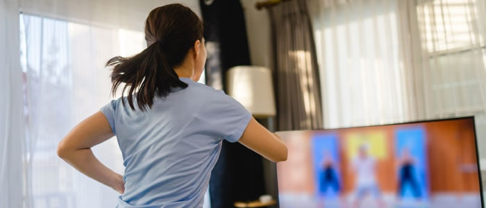 woman learning to dance in her home with a video guide